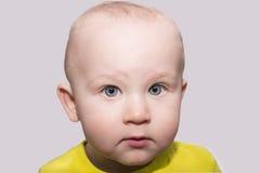 Ernstes blauäugiges Kleinkind, das Kamera betrachtet Stockfoto