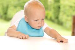 Ernstes blondes Kleinkind in einem blauen bip, das am Tisch sitzt Nebelige Fallinsel Stockfoto