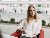 Ernstes blondes Mädchen hält den Tasse Kaffee beim beiseite schauen Der Caféstandort Stockbilder