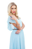 Ernstes blondes Modell im blauen Kleid, das ihre Schulter halten aufwirft Stockfotografie