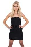 Ernstes blondes Modell im schwarzen Kleid, das Hände auf den Hüften aufwirft Lizenzfreie Stockbilder