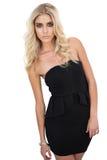 Ernstes blondes Modell im schwarzen Kleid, das Kamera betrachtend aufwirft Lizenzfreie Stockfotos
