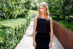 Ernstes elegantes blondes Mädchen im Sommerpark am sonnigen Tag Stockfoto