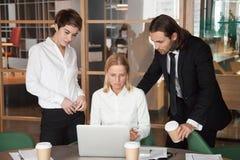 Ernstes fokussiertes Geschäftsteam, das zusammen on-line-Aufgabe herein bespricht stockbild