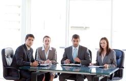 Ernstes Geschäftsteam, das um eine Tabelle sitzt Lizenzfreies Stockfoto