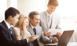 Ernstes Geschäftsteam mit Tablet-Computern, Dokumente, die Diskussion im Büro haben lizenzfreies stockfoto