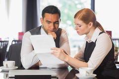 Ernstes Geschäftsteam, das in einem Café zusammenarbeitet Lizenzfreies Stockbild