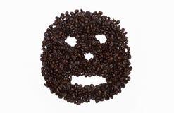 Ernstes Gesicht in den Kaffeebohnen Stockfotos