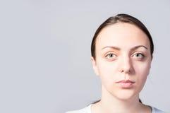 Ernstes Gesicht einer Frau gegen hellen Gray Wall Lizenzfreie Stockfotografie