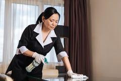 Ernstes hart arbeitend Stubenmädchen, welches die Tabelle sauber macht Lizenzfreie Stockbilder
