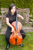 Ernstes jugendlich spielendes Cello draußen Stockbilder