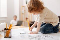 Ernstes Jungenzeichnungsbild auf dem Papier lizenzfreie stockbilder