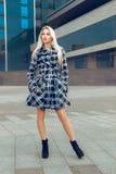 Ernstes junges blondes Mode-Modell im Mantel, der draußen a aufwirft Lizenzfreie Stockbilder