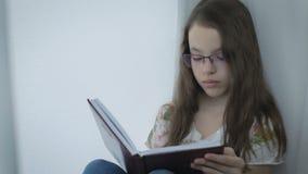 Ernstes kleines Mädchen in den Gläsern tut mit Sorgfalt seine Hausarbeit am Fenster stock video footage