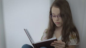Ernstes kleines Mädchen in den Gläsern tut mit Sorgfalt seine Hausarbeit am Fenster stock video
