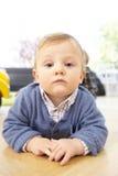 Ernstes Kleinkind, das auf dem Fußboden liegt Lizenzfreie Stockbilder