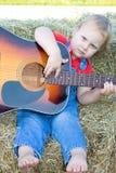 Ernstes Kleinkind, welches die Gitarre spielt. Stockbild