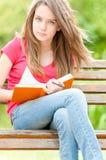 Ernstes Kursteilnehmermädchen, das auf Bank mit Buch sitzt Stockbild