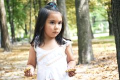Ernstes lateinisches Kind, das zwei Hälften eines Plätzchens in jeder Hand hält Lizenzfreie Stockfotos