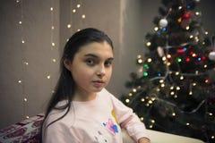 Ernstes Mädchen auf Sofa nahe Weihnachtsbaum Stockfoto