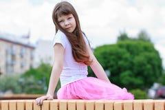 Ernstes Mädchen, das auf einer Holzbank sitzt Lizenzfreie Stockfotografie