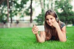 Ernstes Mädchen, das Telefon zur Mitteilung interessiert betrachtet, die sie empfing stockbild