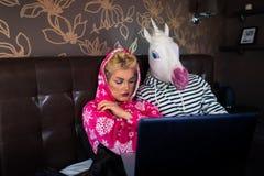 Ernstes Mädchen liegt auf Bett mit merkwürdigem Freund in der lustigen Maske Lizenzfreies Stockfoto