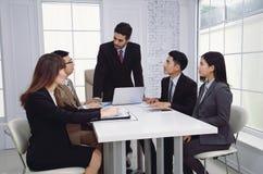 Ernstes multiethnisches Geschäftsteam, das Geistesblitz in modernem O hat Lizenzfreies Stockfoto