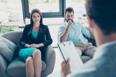 Ernstes Paar hört auf ihren Hausarzt, konzentriert stockfoto