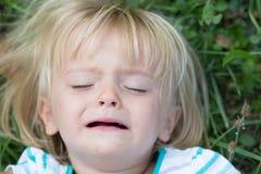 Ernstes schreiendes Leutemädchen-Abschlussporträt des traurigen jungen Babys kaukasisches blondes wirkliches im Freien Lizenzfreies Stockfoto