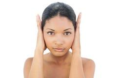 Ernstes schwarzes behaartes Modell, das ihre Ohren blockiert Stockbild