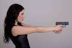 Ernstes sexy Frauenschießen mit dem Gewehr lokalisiert auf Weiß Lizenzfreies Stockfoto