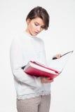 Ernstes starkes junges weibliches Schauen durch die Dokumente in den Ordnern Lizenzfreie Stockfotos
