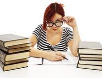 Ernstes Studentenmädchen, das über der Spitze ihrer Gläser schaut Stockbild