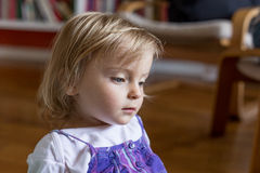 Ernstes trauriges oder denkendes kaukasisches blondes Mädchenporträt des jungen Babys zu Hause Stockbild