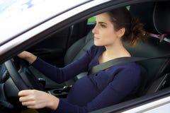 Ernstes treibendes Auto der schwangeren Frau, das Rad hält stockfotografie