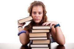 Ernstes und schönes Mädchen, mit einem Stapel Büchern lizenzfreie stockfotografie