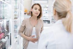 Ernsthafte besorgte Frau, die unter Magenschmerzen leidet lizenzfreie stockfotos