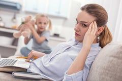 Ernsthafte wütende Mutter, die mit Arbeit überlastet Stockfotografie