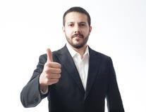 Ernsthafter junger Geschäftsmann, der Zustimmungszeichen zeigt Lizenzfreie Stockfotografie