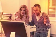Ernsthafter Mann und Frau begeistert, um die großen Ergebnisse ihrer Arbeit zu sehen stockfotografie