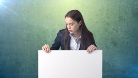 Ernstig Bedrijfsvrouwenportret met lege witte raad op groen Vrouwelijk model met lang haar Royalty-vrije Stock Foto's