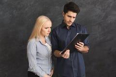 Ernstig couplereading document op grijze achtergrond stock foto