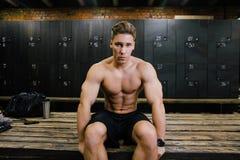 Ernstig geschiktheidsmodel van een zitting van de bodybuilder mannelijke trainer op een bank in de kleedkamer stock fotografie