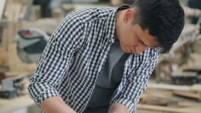Ernstig houthakker het oppoetsen stuk van hout met elektrische schuurmachine die alleen werken stock footage