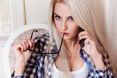 Ernstig jong blondemeisje met blauwe ogen die telefoon spreken Stock Afbeelding