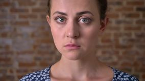Ernstig kalm close-upgezicht van donkerbruine Kaukasische vrouw die ner bakstenen muur zich binnen bevindt stock videobeelden