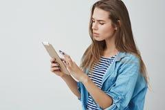 Ernstig-kijkt de bezige aantrekkelijke jonge succesvolle werknemer van de onderneemsterlezing meldt studie discussienota's via di stock foto's