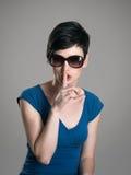Ernstig kort haarbrunette die zonnebril met vinger op haar gebaar van de lippenstilte dragen Stock Foto