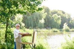 Ernstig mannelijk kunstenaarsholding borstel en het schilderen beeld op schildersezel op openlucht stock afbeeldingen